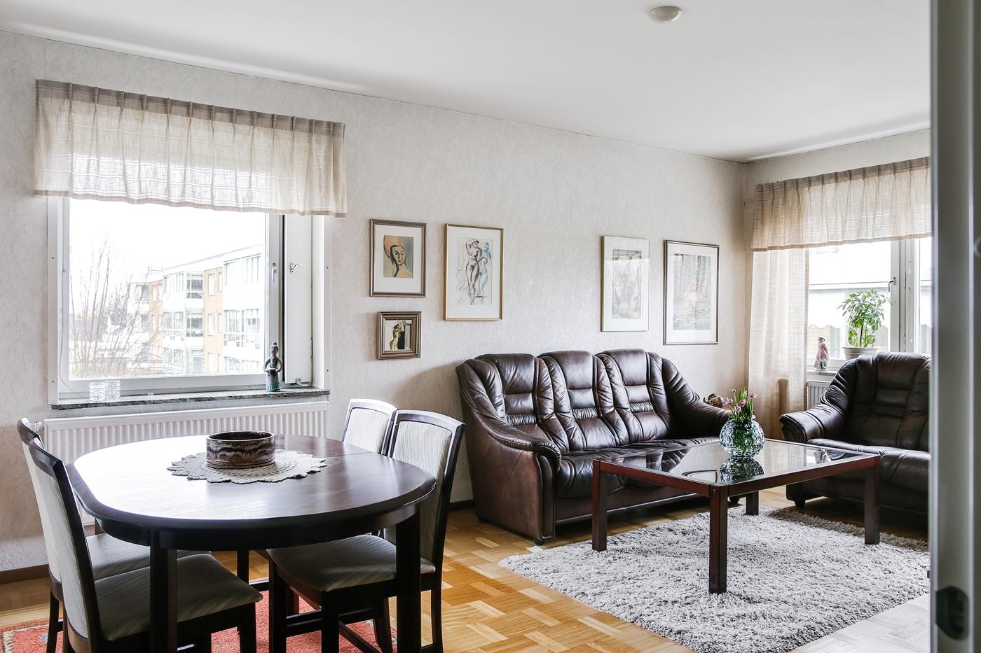 Stort och ljust vardagsrum med fönster i två riktningar.