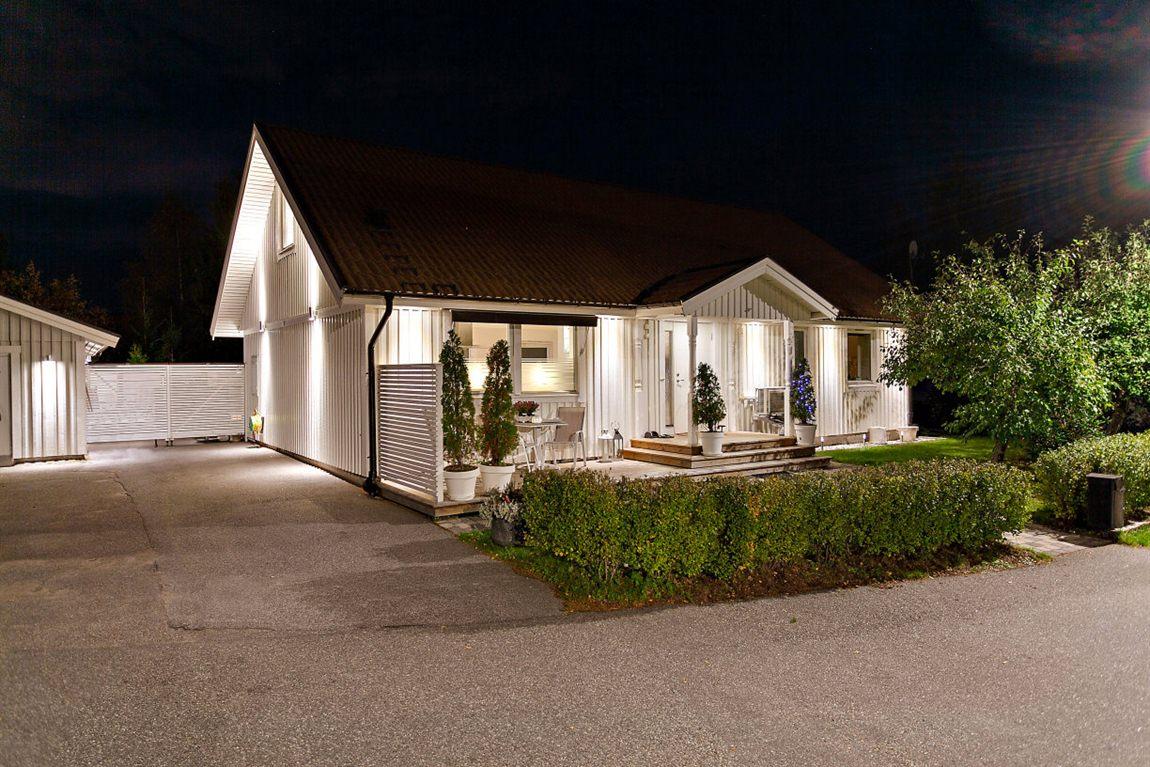 Kvällsbild på huset med dess fina fasadbelysning