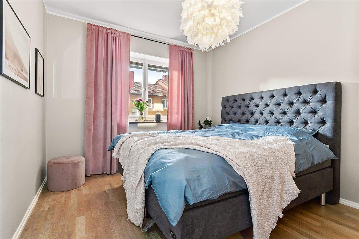 Ljust och väl tilltaget sovrum med nylagt golv och nymålade väggar